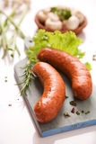 Sausages. Two sausages on wooden cutting board Royalty Free Stock Images