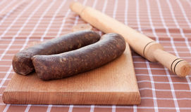 Sausages. Raw,home made sausages ready to be rolled with rolling-pin on wooden chopping board Royalty Free Stock Photography