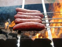 Sausages. The beaded on sticks broil on a fire Royalty Free Stock Photos