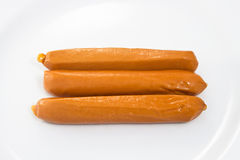 Sausages. Three sausages on white dish Royalty Free Stock Photos
