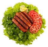 Sausages. Delicious sausages laid on lettuce leaves with tomato slices and parsley Royalty Free Stock Image
