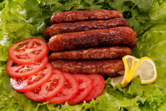 Sausages. Delicious sausages laid on lettuce leaves with tomato slices and parsley Stock Images