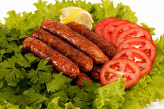 Sausages. Delicious sausages laid on lettuce leaves with tomato slices and parsley Stock Photography