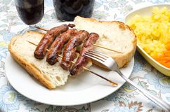 Sausages. Roasted skewers of sausage on the table Royalty Free Stock Photo