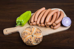 Sausages arranged on cutting board with baguette Stock Photography