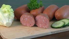 Sausages arranged on cutting board with lettuce stock footage