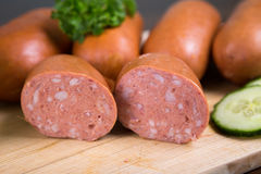 Sausages arranged on cutting board with lettuce Stock Images