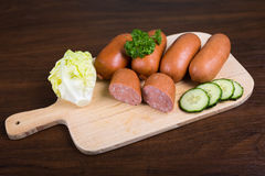 Sausages arranged on cutting board with lettuce Royalty Free Stock Image