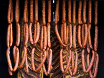 Sausages and bacon being smoked. Sausages and bacon in smoker Royalty Free Stock Photos