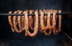 sausages and bacon being smoked barrel-shaped smoker Stock Photography