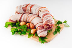 Sausages in bacon on a board Stock Images