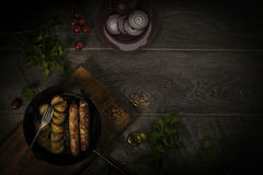 Sausages and baked potatoes in a cast-iron frying pan. A simple peasant breakfast. Top view. Horizontal arrangement. Place under t Royalty Free Stock Photo