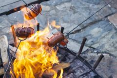 Sausages baking over camp fire. Party with friends royalty free stock photos