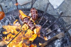 Sausages baking over camp fire. Party with friends royalty free stock photography