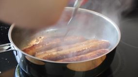 Sausages baking in a pan stock video footage