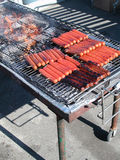 Sausages on Barbecue. Sausages on large barbecue before ballgame stock image