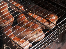 Sausages on a barbecue. Sausages cooking on a barbecue grill stock image
