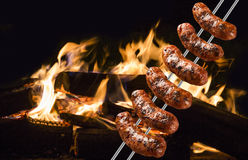 Sausages on the barbecue spit with flames Stock Photo