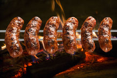 Sausages on the barbecue spit with flames Royalty Free Stock Photo