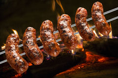 Sausages on the barbecue spit with flames Royalty Free Stock Photos