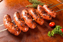 Sausages on the barbecue spit on wooden background Royalty Free Stock Image