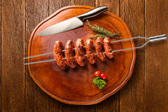 Sausages on the barbecue spit on wooden background Royalty Free Stock Images