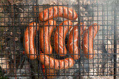 Sausages on BBQ. Tasty juicy sausages on barbeque Royalty Free Stock Images