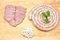 Sausages beef meat slices and beans. Spiral shaped sausages, beef meat slices, beans and parsley leaves on wooden board Royalty Free Stock Photography