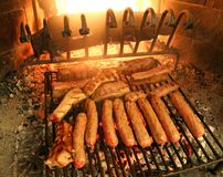 Sausages and beef steaks cooked on the grill of a fireplace. In a mountain cabin stock photo