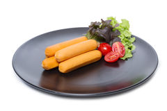 Sausages on black dish with fresh vegetable isolated on white Royalty Free Stock Photo