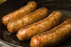 Sausages in a black frying pan royalty free stock photo