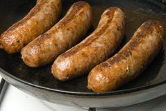 Sausages in a black frying pan with gas stove Royalty Free Stock Photo