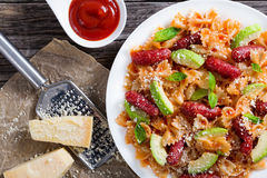Sausages bowtie Pasta warm salad with avocado slices Royalty Free Stock Photos