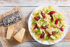 Sausages bowtie Pasta warm salad with avocado slices and cheese Stock Image