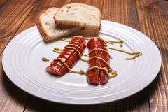 Sausages and bread with Dijin mustard on plate Royalty Free Stock Photos