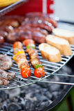 Sausages, bread and shashliks on grill Stock Photography
