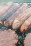 Sausages and burgers on barbecue. Sausages and burgers cooking on barbecue grill Stock Photos