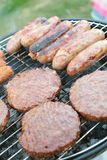 Sausages and burgers on barbecue. Sausages and burgers cooking on barbecue grill Stock Photography