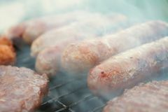 Sausages and burgers on barbecue Royalty Free Stock Photography
