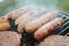 Sausages and burgers on barbecue Stock Photo
