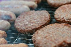 Sausages and burgers on barbecue Royalty Free Stock Image
