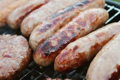 Sausages and burgers on barbecue. Sausages and burgers cooking on barbecue grill Royalty Free Stock Images