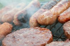 Sausages and burgers on barbecue. Sausages and burgers cooking on barbecue grill Royalty Free Stock Photo