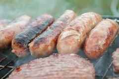 Sausages and burgers on barbecue Stock Photos