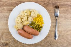 Sausages with cauliflower, sweet corn, green peas and fork Royalty Free Stock Image