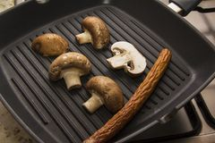 Sausages and champignons on iron pan Royalty Free Stock Image