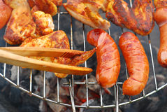 Sausages and chicken wings on the grill Royalty Free Stock Photo