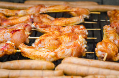 Sausages and chicken wings on smoking grill barbeque Royalty Free Stock Photos