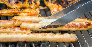 Sausages and chicken wings on smoking grill barbeque Royalty Free Stock Images