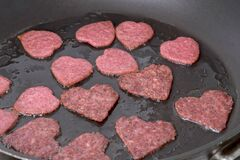 Sausages chorizo salami in the shape of a heart fried in the pan. Homemade food idea for Valentines Day and Mothers Day